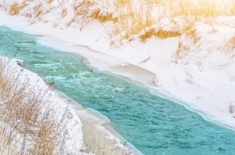 Rough river at the foot of the mountains in a turquoise, blue, green forest in winter, ice and snow around the landscape. stock photos