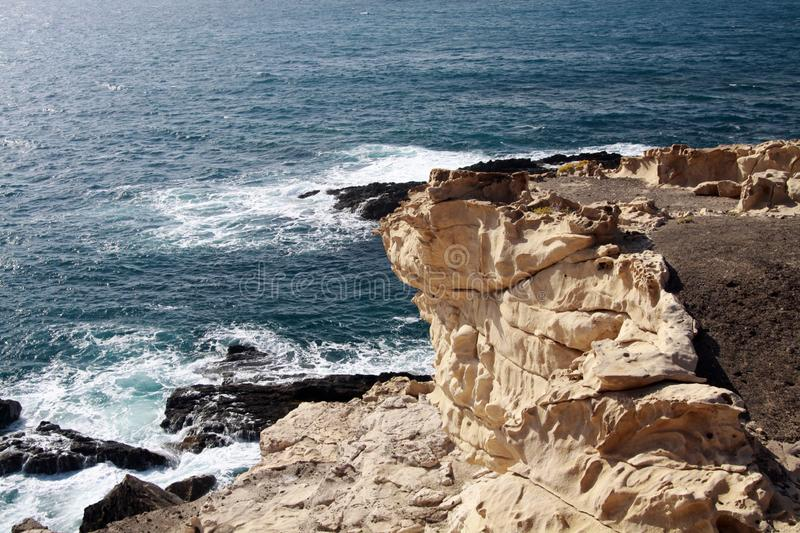 Rough rocky coast with rugged sharp cliffs and strong current in North-West of Fuerteventura, Canary Islands, Spain. Panoramic view on Rough rocky coast with stock photo