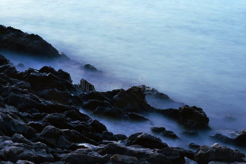 Soft misty blue water against rough dark rocks royalty free stock photos