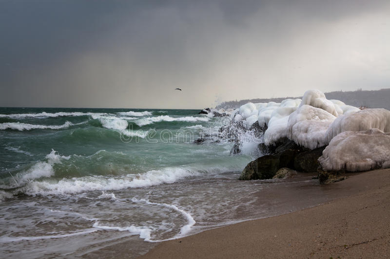 Rough sea and frozen ice. Rough sea during winter storm with frozen ice on the shore stones royalty free stock photo