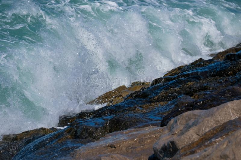 Rough sea and high waves. Crashing on shore aginst rocks boulder boulders danger ocean warning windy stock photo
