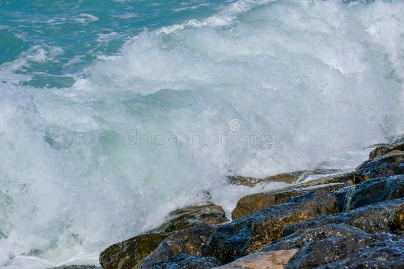 Rough sea and high waves. Crashing on shore aginst rocks boulder boulders danger ocean warning windy stock photography