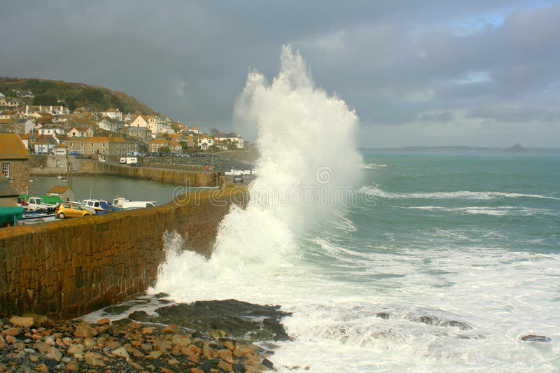 Rough seas at Mousehole. Rough seas breaking over the harbour wall at the port of Mousehole, Cornwall, England royalty free stock photography