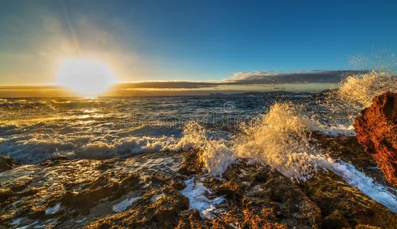 Rough sea by Sardinia rocky shore at sunset. Italy royalty free stock photos