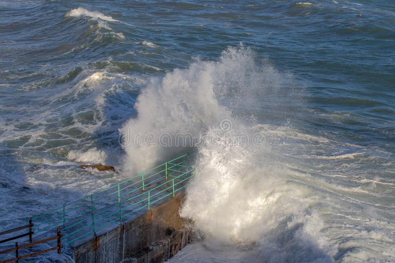 Rough Sea Waves Crashing Over a Pier, mediterranean sea, ligurian coast, Italy. royalty free stock image