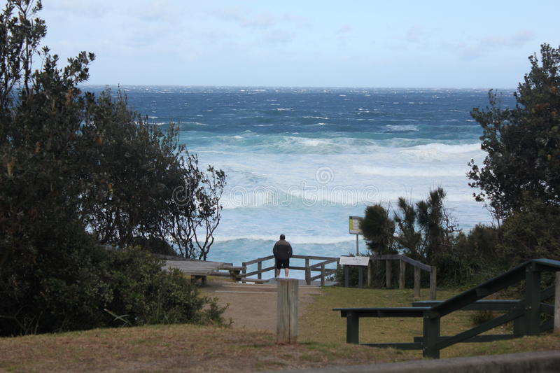 Rough Seas. Man looking on at rough seas from a park stock photos
