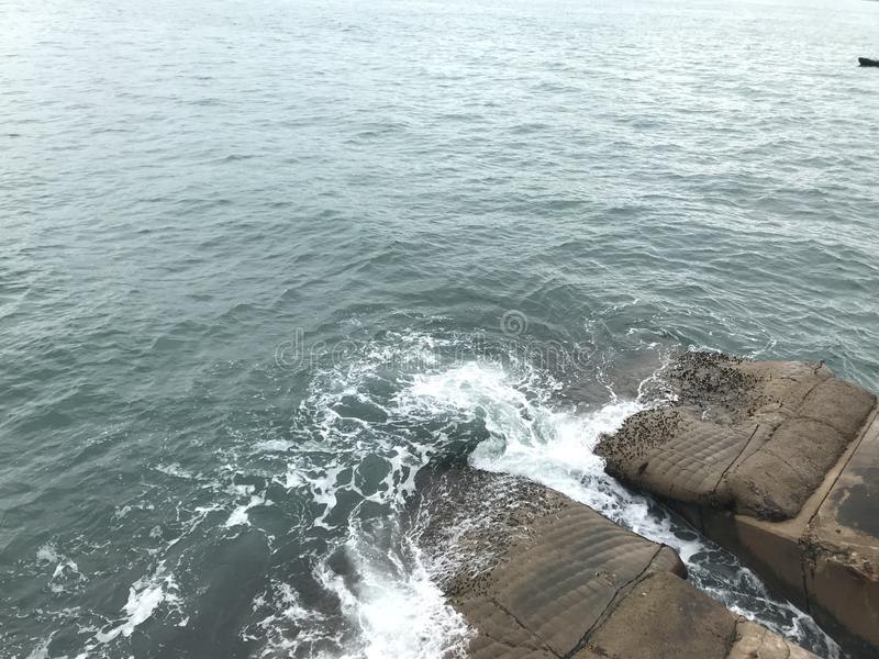 Rough seas on the rock. Rough seas dashing on a big rock on the sea stock images