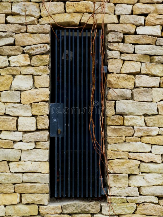 rough split faced white textured stone wall detail with steel grille stock photography