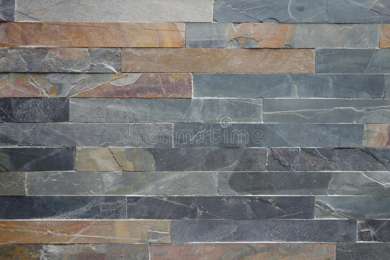 Roughly Textured Stone Cladding Tiled Wall In Grey And Ochre Colours Background