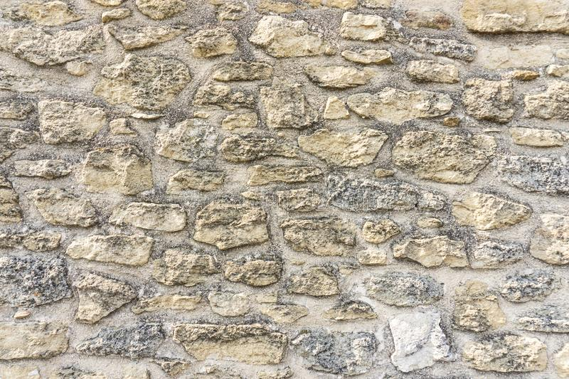 Rough surface of random pattern rastic of brown and light yellow color natural free form sand stone cladding on the concrete wall stock photo