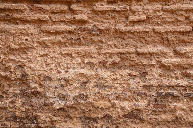 Crumbling brown mud brick wall texture. Rough texture of crumbling traditional old brown mud brick wall royalty free stock image