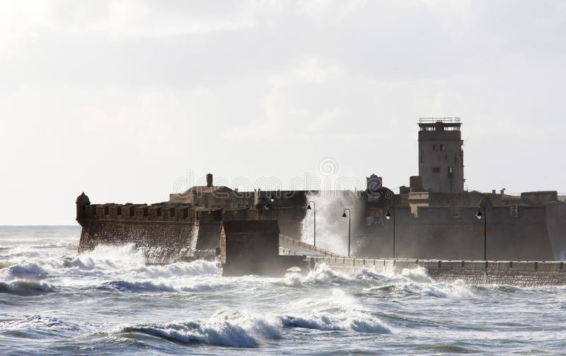 Rough waves around Castle of San Sebastian, Cadiz. The Castle of San Sebastian is a military fortification, and is situated at the end of a road leading out from royalty free stock image