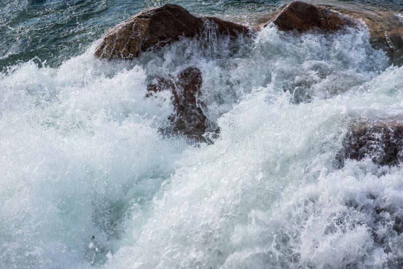 Storm surge waves crashing against shoreline. Rough waves crashing against rocky shoreline royalty free stock image