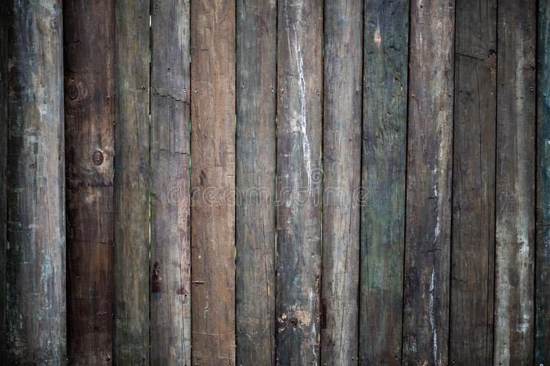 Rough textured multitonal wood fence. Multi-tonal rough textured bare half pole wood solid tropical fence stock images