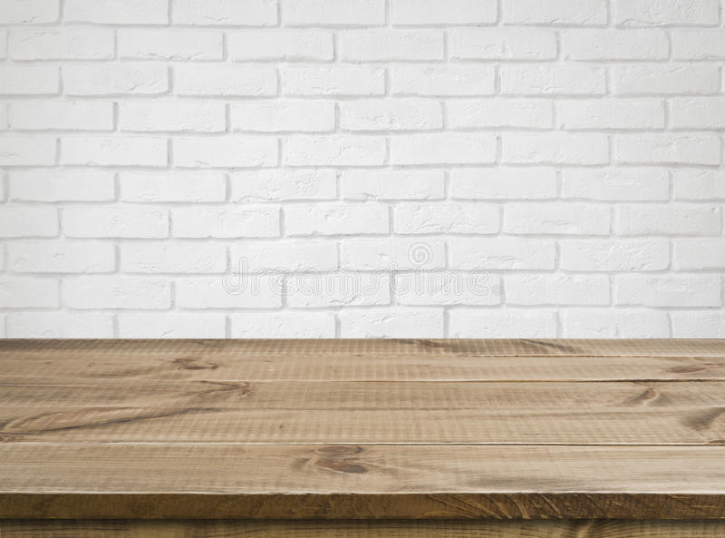Rough wooden texture table over defocused white brick wall background royalty free stock photography