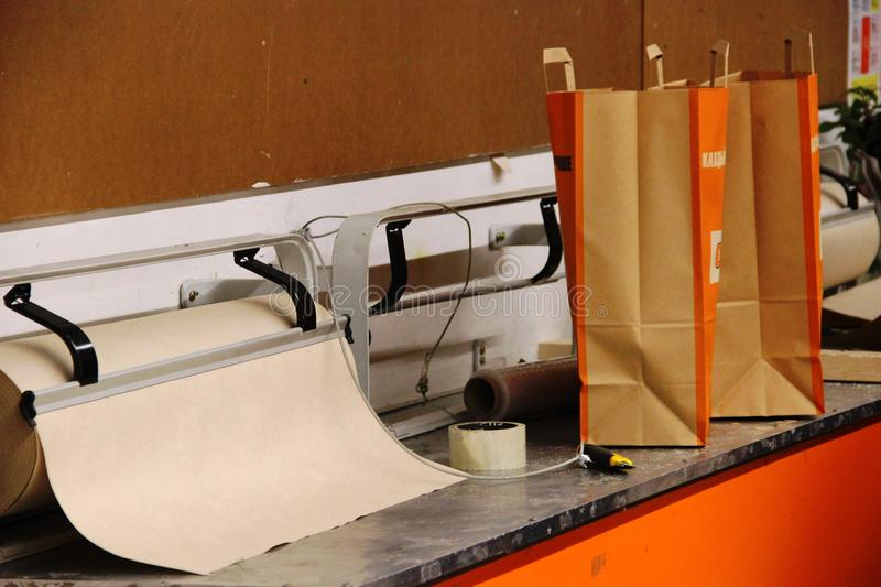 Rough wrapping paper, duct tape, paper knife and paper bags for shopping in the hypermarket, interior in orange tones stock photos