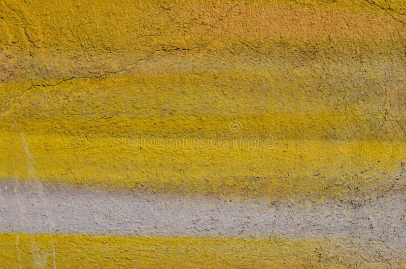 Rough yelllow wall. Rough cracked plastered wall airbrushed with yellow and white paint royalty free stock photography