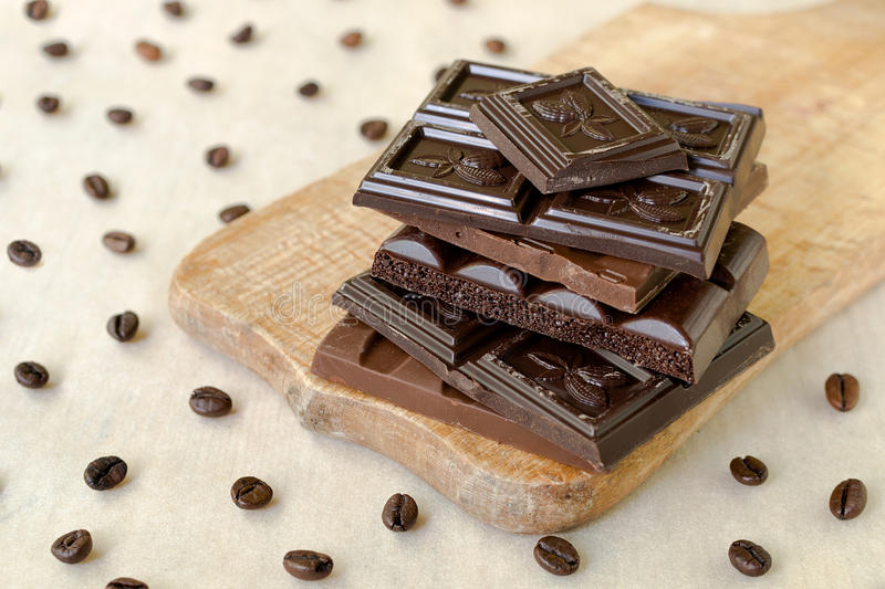 Roughly broken pieces of chocolate are stacked on a wooden board, coffee beans are scattered around royalty free stock images