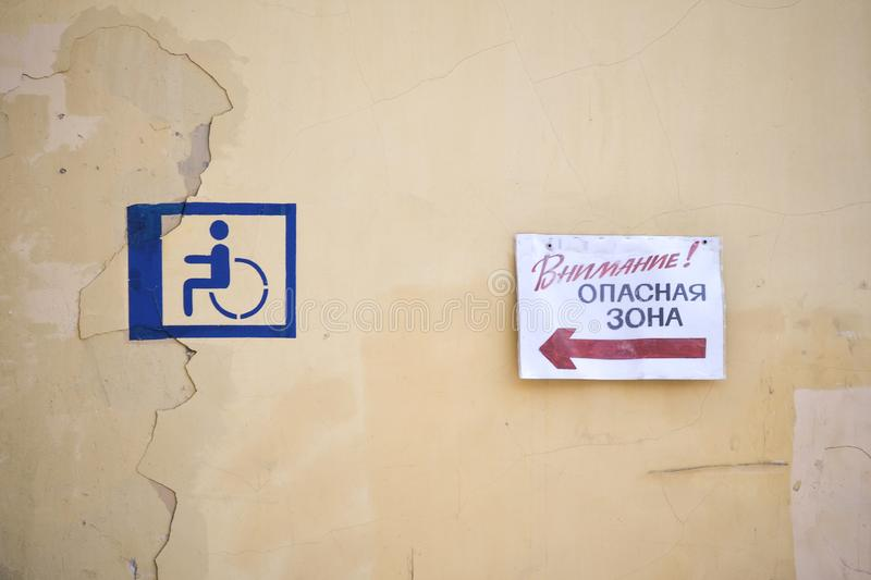 Roughly drawn sign of a disabled person on a yellow wall. The plate with the inscription in Russian. stock photos