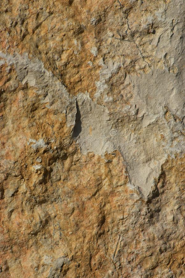 Roughly hewn panel of golden brown and light gray sedimentary rock with tool marks visible. There are pieces broken out of the rock royalty free stock photography