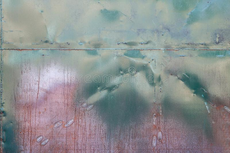 Roughly treated metal surface. Pattern of roughly treated metal surface with notches, dents and rust. Blue, green and cherry shades, unusual texture. Usefull for royalty free stock photography