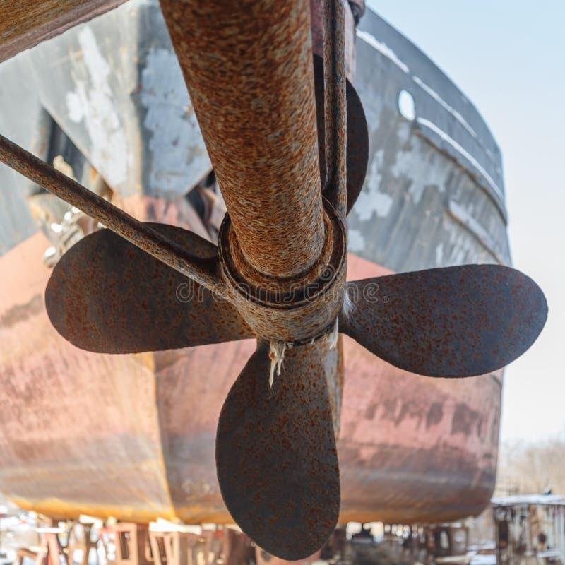 Rouillé et axe contre la coque du bateau, se tenant sur le rivage en prévision de la réparation images stock