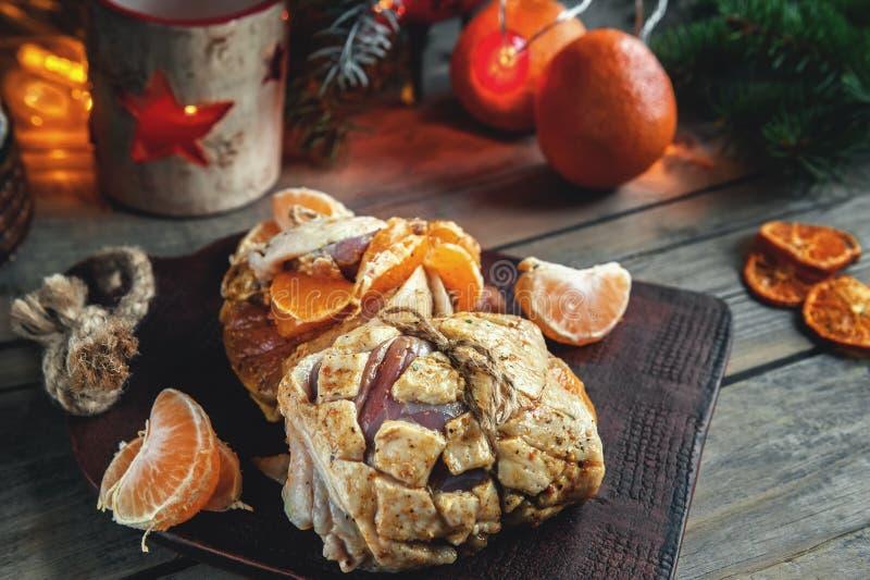 Roulade av filén för andbröst som är välfylld med tangerin som är förberedda för att laga mat på gallret på jultabellen arkivbild