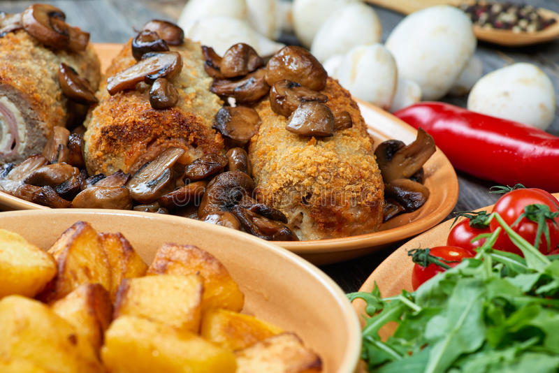 Roulade of pork with roasted mushrooms and potatoes royalty free stock photo