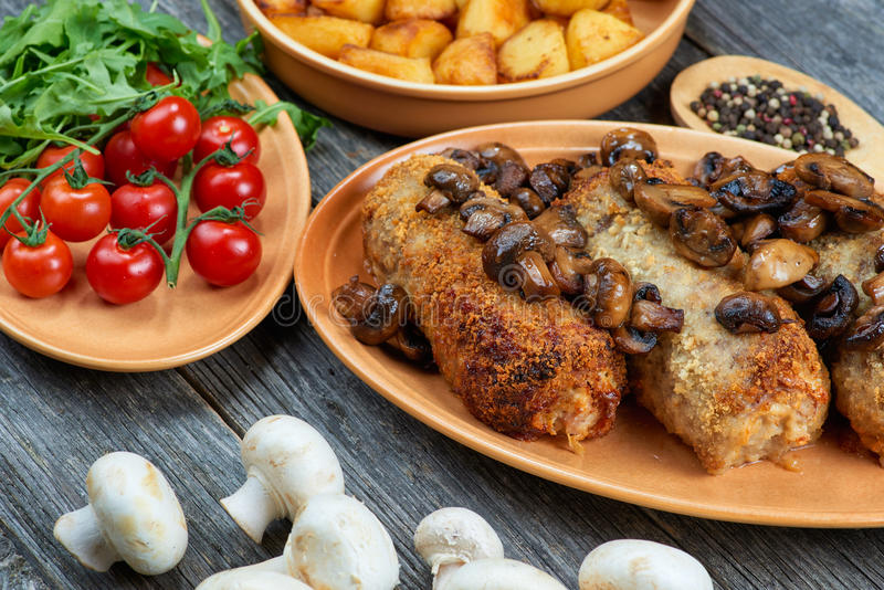 Roulade of pork with roasted mushrooms and potatoes stock photography