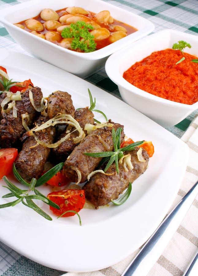 Roulades de viande grillées avec les haricots blancs et la sauce géants images libres de droits