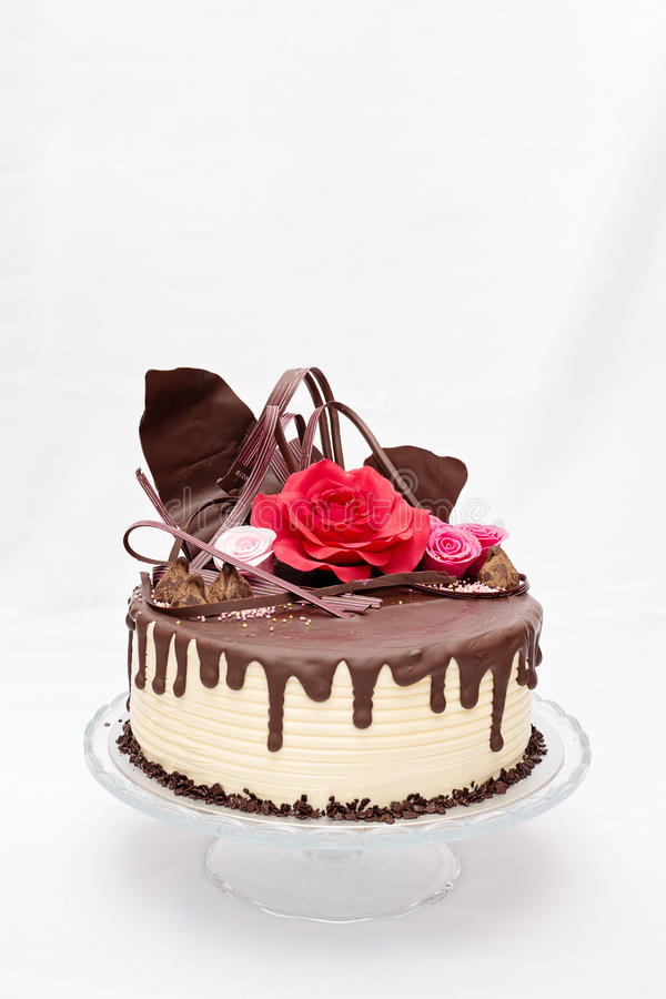 Rould, one layer white and brown chocolate cake. With red and pink edible marzipan flowers on top stock images