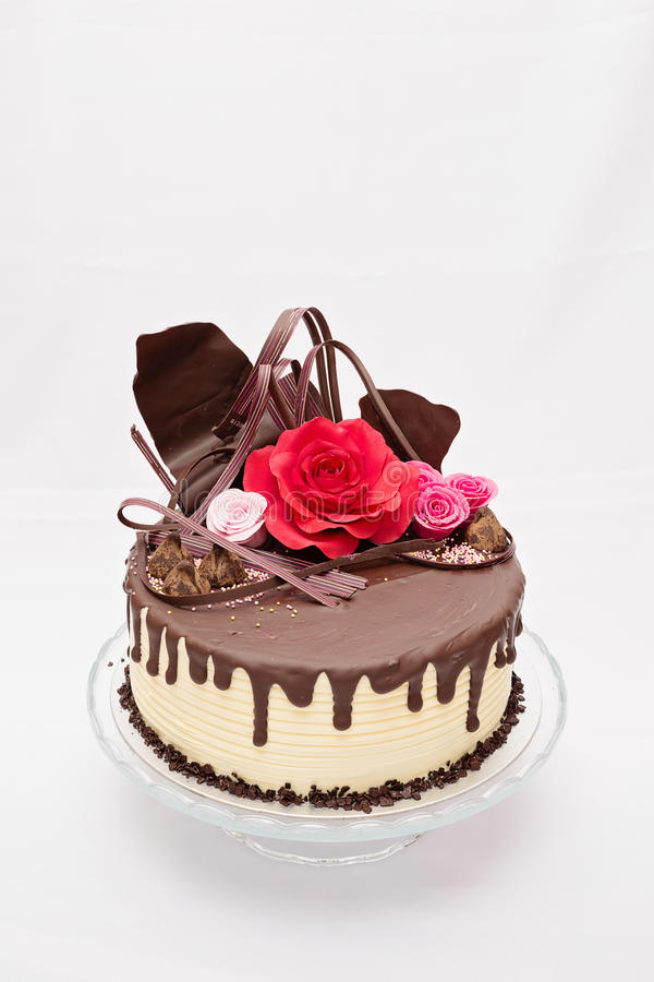 Rould, one layer white and brown chocolate cake. With red and pink edible marzipan flowers on top royalty free stock photography
