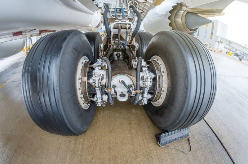 Roule des supports de train d'atterrissage d'arrière de pneu en caoutchouc, sous la vue d'aile photographie stock libre de droits