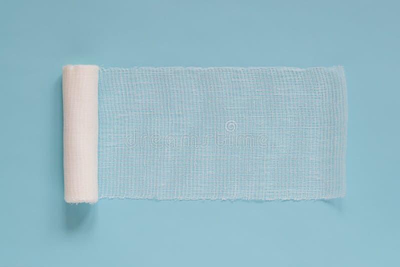 Rouleau déroulé de bandage médical stérile blanc pour habiller des blessures sur un fond bleu, l'espace de copie images libres de droits