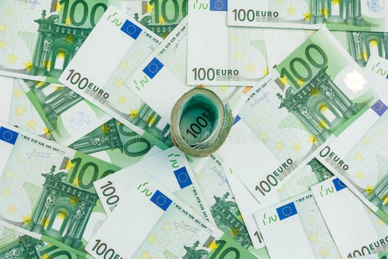 Rouleau d'euro billets de banque, beaucoup de billets de banque 100 de l'euro, le fond européen de devise photographie stock