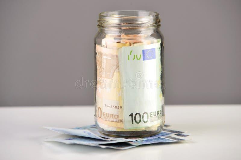 Rouleau d'euro billets de banque dans un pot d'argent images libres de droits