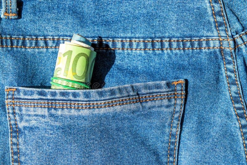 Rouleau d'euro billets de banque dans une poche image stock