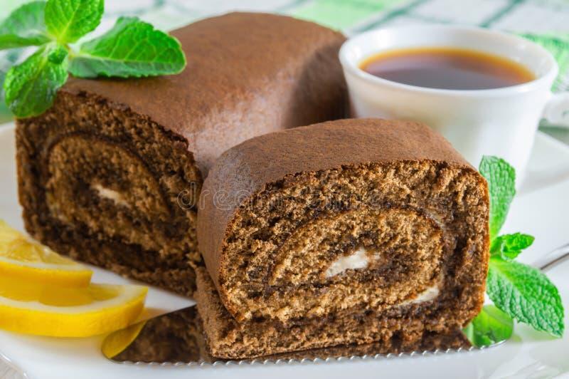 Rouleau de biscuit de chocolat et une tasse de th? avec des tranches de citron photos stock