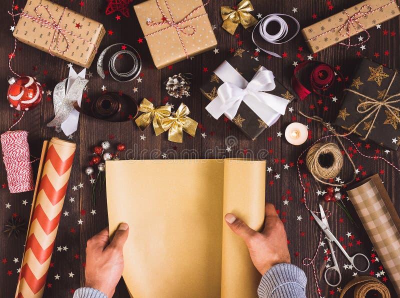 Rouleau de déploiement de main d'homme d'envelopper le papier d'emballage pour le boîte-cadeau de emballage de Noël photos stock