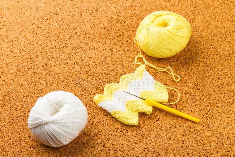 Rouleau de fil à tricoter mou blanc et jaune, tricotant, aiguille photo libre de droits
