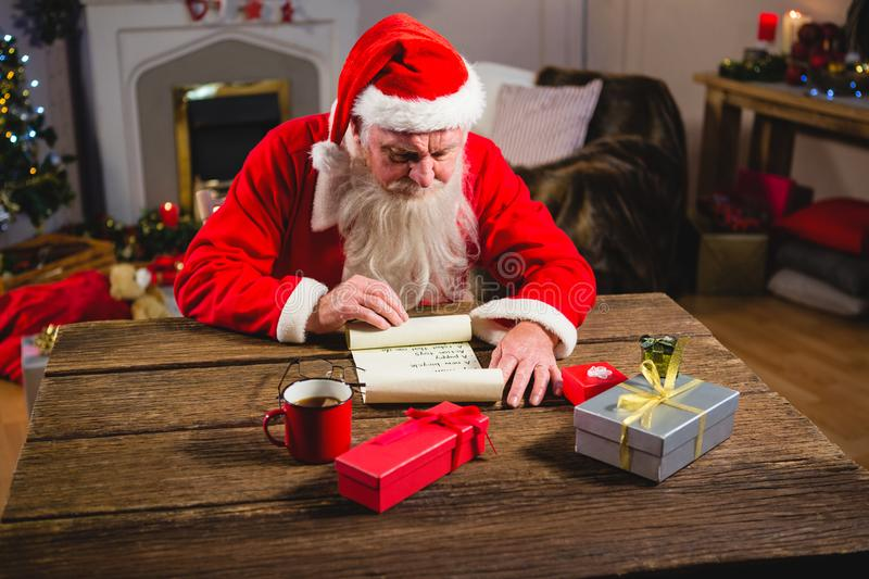 Rouleau de lecture de Santa Claus dans le salon photo stock