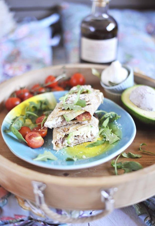 Rouleau de pain pita sur le gril bourrage des poissons et de la salade avocat et huile d'olive dîner sur un plateau en bois Nourr photo libre de droits