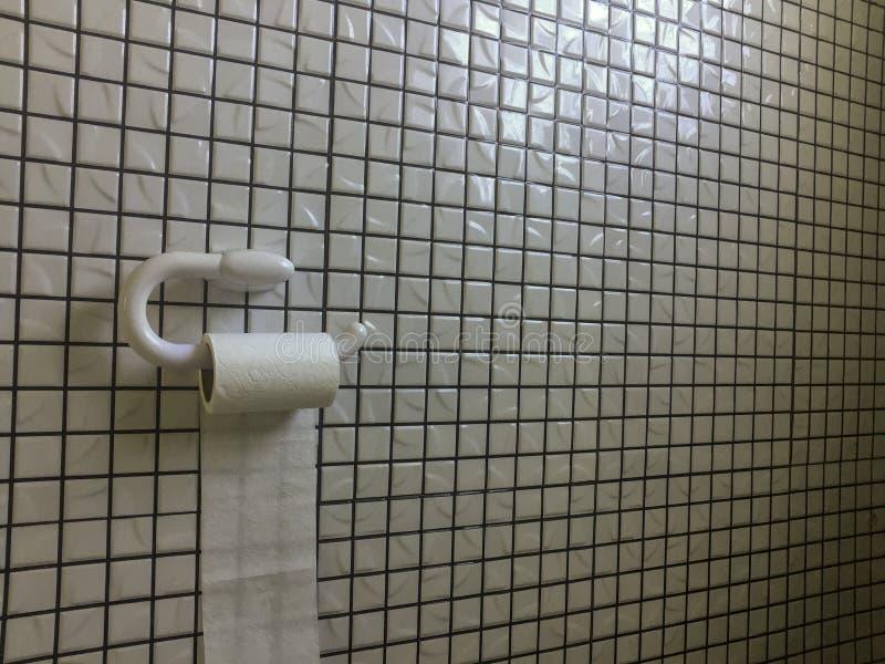 Rouleau de papier hygiénique contre le mur de mosaïque photo stock