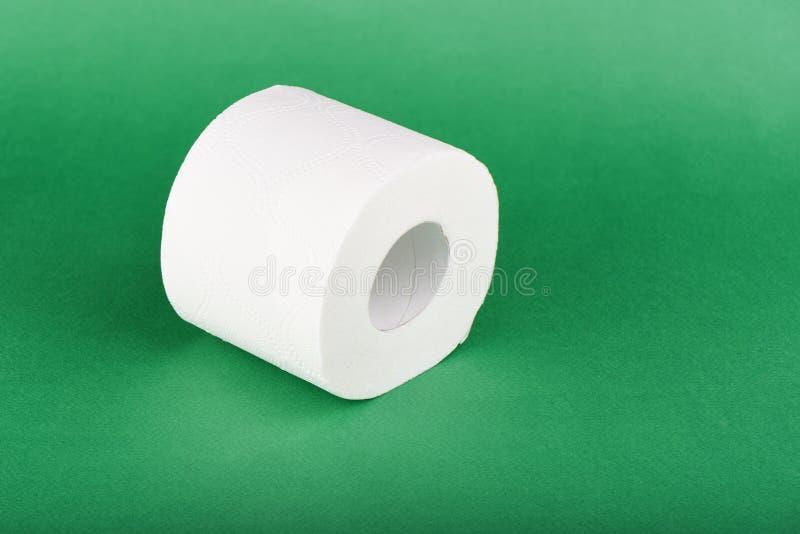 Rouleau de papier hygiénique d'isolement sur le fond vert photographie stock