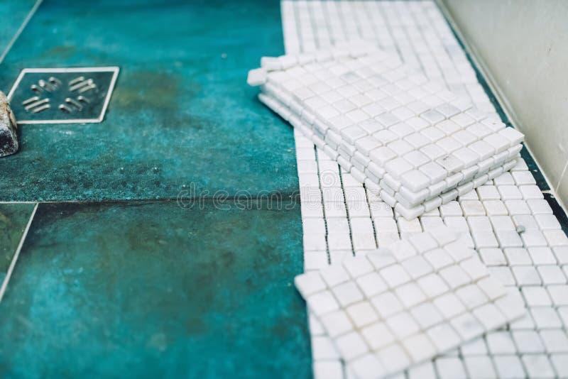 Rouleau de peinture avec des échantillons de peinture Fermez-vous des carreaux de céramique de marbre de mosaïque sur le plancher photographie stock libre de droits
