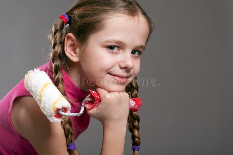 Rouleau de peinture de fixation de petite fille photo stock