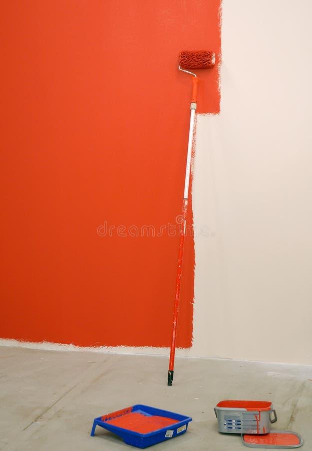 Rouleau de peinture rouge par le mur photo stock