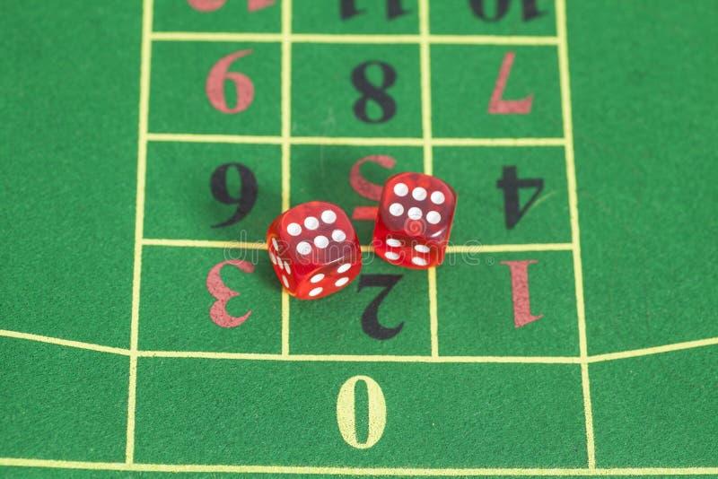 Rouleau des matrices rouges sur une table de jeu photographie stock