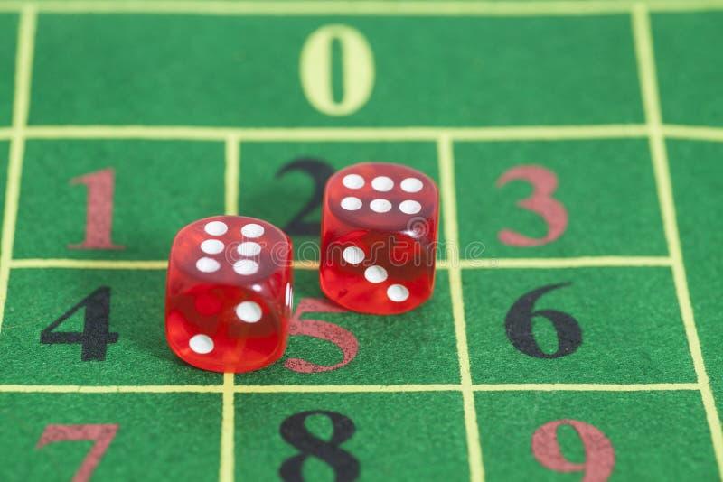 Rouleau des matrices rouges sur une table de jeu photographie stock libre de droits