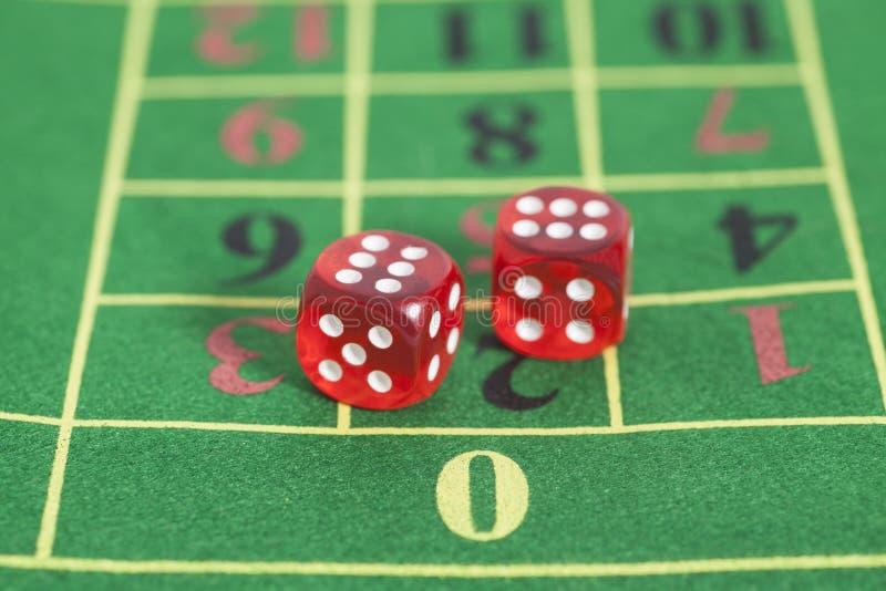 Rouleau des matrices rouges sur une table de jeu dans un casino photographie stock